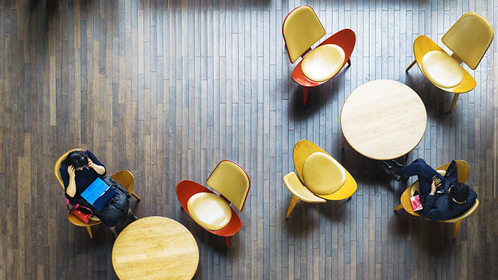 Aerial top view of business people sit on chair with table desk with laptop and book in public space on the interior wood furniture and pattern wood floor.